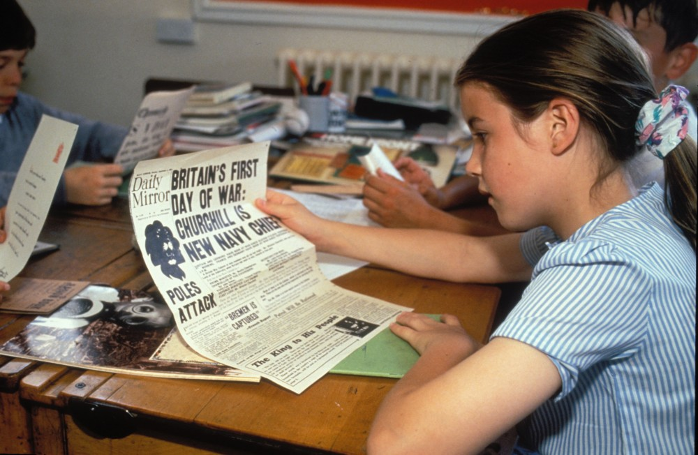 History studies at primary school Pupils studying Second World War by reading old newspaper UK